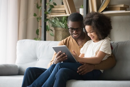 African father holds on lap daughter sitting resting on sofa in living room using digital tablet holding mobile computer watch cartoons educational online program, buying shopping via internet concept Stock Photo