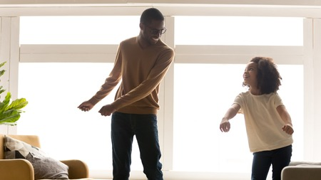 Wide image black family having fun at home standing moving near panoramic window dancing listening favourite energetic song feels happy spend time together, leisure funny activities with child concept Stock Photo