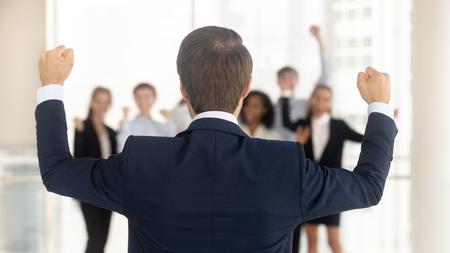Vue arrière du PDG de l'entreprise à succès célébrant la victoire de l'entreprise avec l'équipe de l'entreprise au bureau, l'arrière du chef de file avec les mains levées ravies de la croissance des récompenses pour la réalisation des objectifs de travail