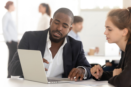 Black salesman broker insurer advisor consulting working with client looking at laptop showing business presentation, african manager mentor having conversation convincing customer instructing intern 版權商用圖片