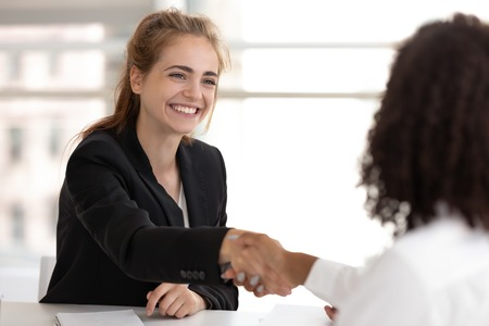 Happy businesswoman hr manager handshake hire candidate selling insurance services making good first impression, diverse broker and client customer shake hand at business office meeting job interview Foto de archivo