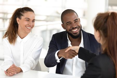 Felice coppia di etnia mista clienti stretta di mano agenti broker fanno un accordo, africano hr stringere la mano del candidato caucasico che assume al colloquio di lavoro, reclutamento e concetto di prestito assicurativo