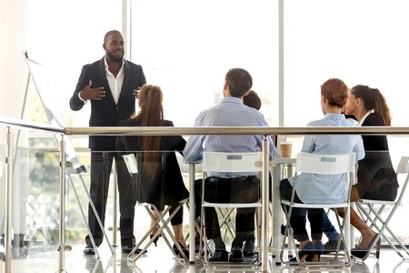 Diverse business team listening flipchart presentation of african manager coach mentor at corporate meeting training, black leader consulting people employees clients at workshop in modern boardroom 스톡 콘텐츠