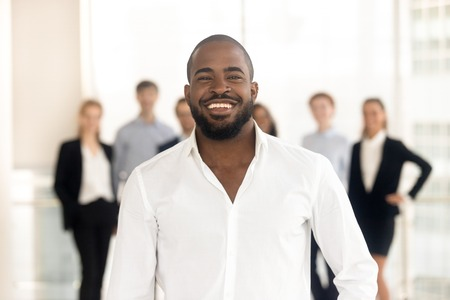 Confident happy african american business coach corporate leader posing with diverse team at background, smiling black ceo manager, male professional executive looking at camera in office, portrait