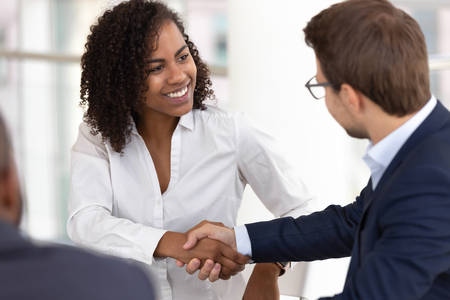 Smiling diverse businesswoman and businessman shake hands make partnership deal agreement at group office meeting negotiation thank for good teamwork expressing respect gender racial equality concept.