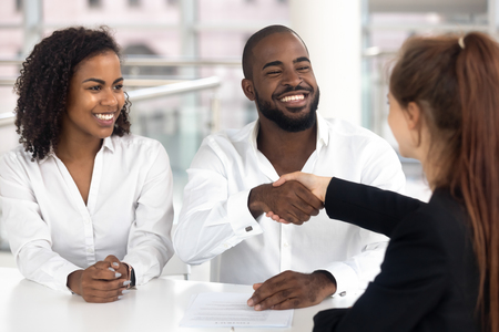 Happy black couple satisfied clients customers handshake bank manager insurer broker take loan buy insurance, african american family buyers signing mortgage investment contract shake realtor hand