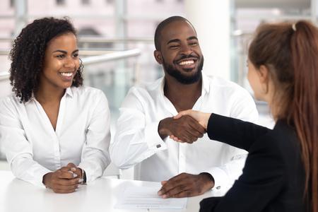 Szczęśliwa czarna para zadowolonych klientów uścisk dłoni kierownik banku ubezpieczyciel pośrednik weź pożyczkę kup ubezpieczenie, afroamerykańscy nabywcy rodziny podpisując umowę inwestycyjną hipoteczną wstrząsnąć pośrednikiem w handlu nieruchomościami