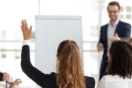Der Schulungsteilnehmer hebt die Hand und stellt eine Frage, beteiligt sich an der Abstimmungsinitiative beim Teamworkshop der Mitarbeiter, Unternehmenswissen, Geschäftsbildung, Konzept der freiwilligen Beteiligung, Rückansicht