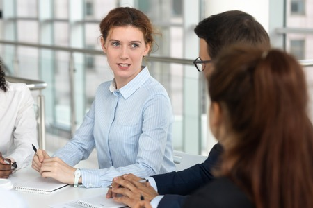 Female negotiator coach mentor leader speaking at group negotiations, businesswoman manager presenter teaching staff instructing interns explaining benefits to clients at team office meeting workshop Stock Photo