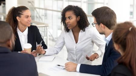 Equipo de negocios escuchando al entrenador de empresaria africana hablando en la capacitación explicando la estrategia corporativa, mentor de raza mixta hablando en una reunión grupal que instruye a los empleados que consultan a diversos clientes