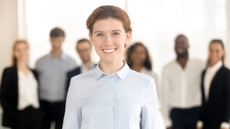 Young happy female work leader, woman company ceo, office employee looking at camera posing with diverse team, smiling professional executive manager businesswoman boss, hr or business coach portrait