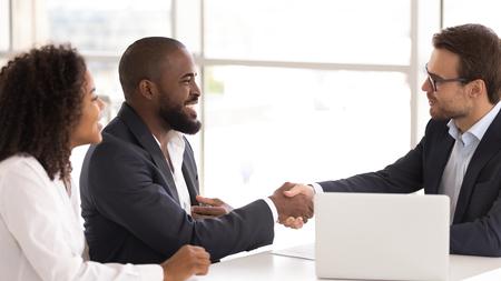 Gelukkig afro-amerikaans stel schudt hand van verzekeraar verkoper koopt verzekeringsdiensten, zwarte familie klanten klanten handdruk kaukasische makelaar maakt verkoop koopovereenkomst overeenkomst nemen banklening