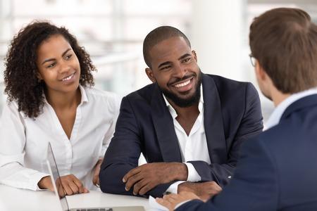 Glückliches afroamerikanisches junges Familienpaar hört Agenten-Versicherungsverkäufer zu, die schwarze Kunden beim Treffen beraten, Bankmanager-Agent, der mit Kunden spricht, die den Versicherungskredit-Hypothekenvertrag erklären