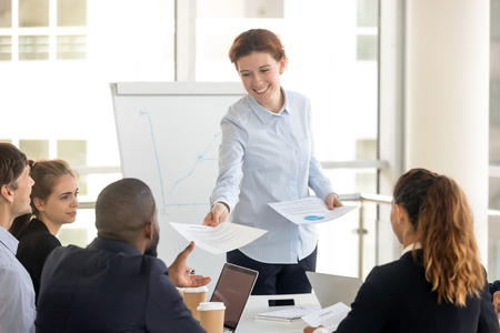 Female manager presenting paper report giving business plan to diverse employees clients at office group meeting, company leader and workers team doing paperwork at corporate briefing in boardroom