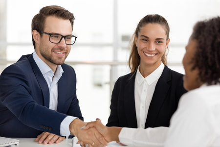 Happy caucasian hr handshaking hiring successful african job candidate at business interview, smiling manager shake hand employ client make services deal good first impression, human resource concept Фото со стока