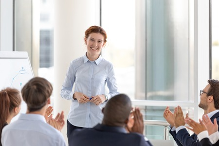 Grateful business audience applauding speaker coach thanking for conference seminar presentation, diverse happy office people group clap hands appreciating training lecture congratulating presenter