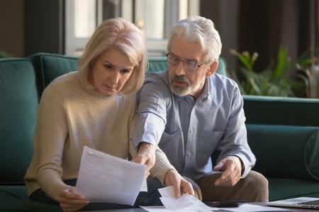 Grave pareja madura de pelo gris calculando facturas, comprobando las finanzas juntos en casa, ancianos jubilados leyendo documentos de la familia, documentos de seguros, preocupados por préstamos, quiebras o problemas de dinero