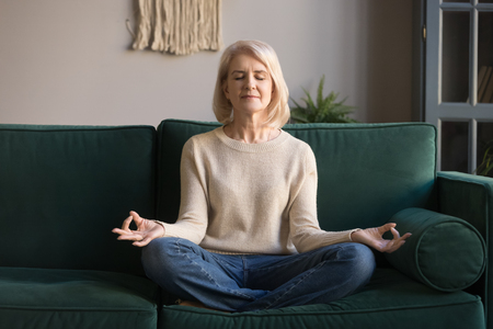 Grey haired mature woman meditating, practicing yoga at home, middle aged female with closed eyes sitting in lotus pose on comfortable couch, breathing, relaxing for mental balance, free weekend