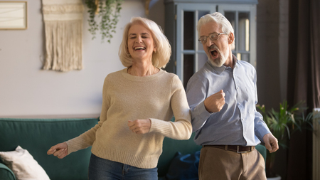 Excited mature couple, laughing grey haired man and woman having fun, dancing to favorite music at home in living room, middle aged wife and husband spending weekend together, funny activity 스톡 콘텐츠