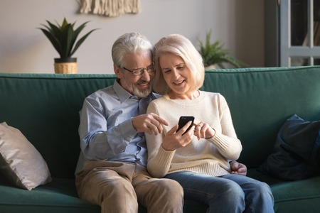 Happy mature family, wife and husband using phone together at home, smiling middle aged man and woman sitting on couch, using mobile device apps, watching video in social network, surfing internet Stock Photo