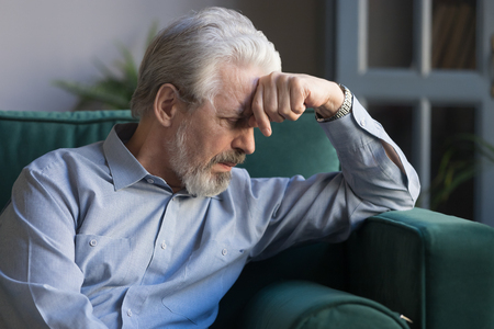 Unhappy lonely grey haired mature man sitting on couch alone, holding head on hand, sad old husband missing wife, upset middle aged male lost in thoughts, elderly and loneliness concept close up 版權商用圖片