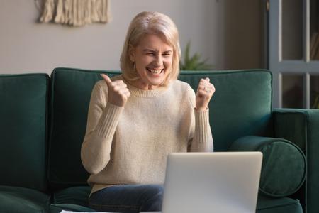 Feliz emocionada mujer madura de pelo gris celebrando la victoria en línea, usando la computadora portátil, mirando la pantalla, sentada en el sofá en casa, mujer de mediana edad sintiéndose asombrada, sorprendida por increíbles buenas noticias