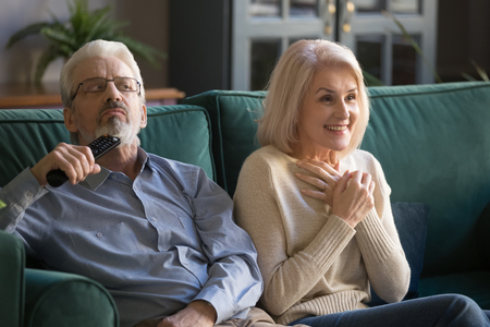 Aged couple, mature wife and husband watching tv show, series, drama or melodrama movie together at home, senior family enjoying weekend, bored man and smiling fascinated woman sitting on couch