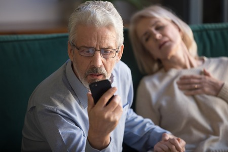 Unhappy mature man, husband calling emergency, holding wife hand, looking on phone screen, woman having heart attack, touching chest, suffering from heartache disease at home, feeling pain