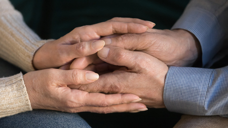 Close up middle aged wife holding husband hands, showing support and love, expressing sympathy and understanding, mature couple, family enjoying moment, elder woman caressing, comforting man