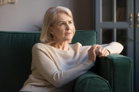 Verstoorde nadenkende grijsharige volwassen vrouw die zich zorgen maakt over problemen, gefrustreerde vrouw van middelbare leeftijd die wegkijkt, denkend aan eenzaamheid, peinzende depressieve senior vrouw die alleen op de bank zit Stockfoto