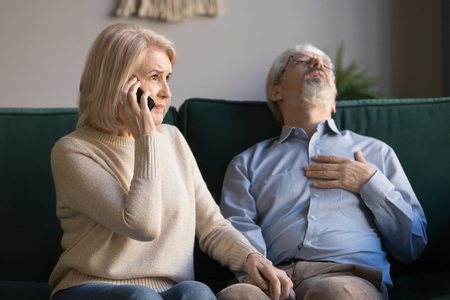 Mature woman, wife calling emergency, talking on phone, holding old husband hand, grey haired man having heart attack, touching chest, suffering from heartache disease at home, feeling pain Stock Photo