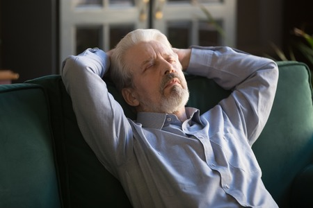 Sleeping middle aged man with closed eyes relaxing on comfortable sofa at home, grey haired carefree grandfather with hands behind head daydreaming, no stress peaceful free time at home close up