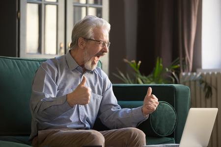 Feliz hombre maduro de pelo gris con gafas gritando, celebrando el éxito, victoria en línea, apuesta exitosa, usando la computadora portátil, sentado en el sofá en casa, mirando la pantalla, hombre de mediana edad emocionado por las buenas noticias Foto de archivo