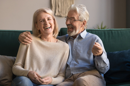 Portrait of middle aged laughing man and woman at home, excited mature family having fun together, grey haired husband and wife embracing, sitting on cozy sofa, posing for photo, enjoying weekend