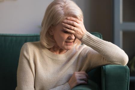 Malheureuse femme mûre aux cheveux gris souffrant de maux de tête, de douleur, de front touchant, d'attaque de panique, a reçu de mauvaises nouvelles, grand-mère d'âge moyen déprimée assise seule sur un canapé à la maison, gros plan