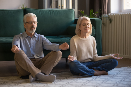 Calm middle aged couple practicing yoga together, meditating at home, grey haired man and woman with closed eyes sitting in lotus pose on floor in living room, breathing, relaxing for mental balance Stock Photo