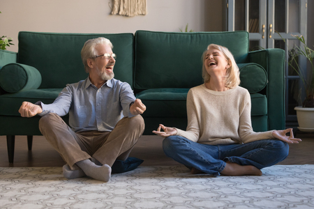 Happy mature couple having fun, practicing yoga together at home, laughing grey haired man and woman sitting in lotus pose on floor in living room, breathing, relaxing, healthy lifestyle concept Stock Photo