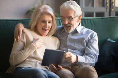 Surprised mature wife and husband looking at screen, using tablet at home, reading pleasant unexpected news together, aged family sitting on couch, middle age woman and man embracing, watching video