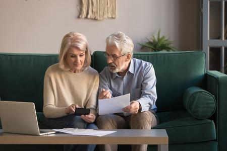 Poważna dojrzała para obliczająca rachunki do zapłaty, sprawdzająca finanse krajowe, zarządzanie rodziną w średnim wieku, planowanie budżetu, wydatki, siwy mężczyzna i kobieta czytający dokumenty kredytu bankowego w domu Zdjęcie Seryjne