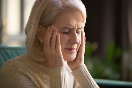 Close up grey haired mature woman suffering from headache or dizziness, touching massaging temples, calming down, feeling strong pain, migraine, tired middle aged female having health problem
