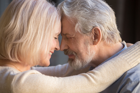 Romantic mature couple in love, wife and husband face to face, middle aged family enjoying tenderness and closeness, grey haired man and woman with closed eyes touching foreheads, close up Archivio Fotografico
