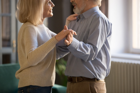 Middle aged couple, loving wife and husband dancing at home in cozy living room, grey haired spouses celebrating anniversary, mature man and woman dating, spending time together, close up Stock Photo