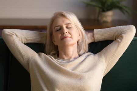 Calma mujer de mediana edad relajante disfrutando de fin de semana en un cómodo sofá, abuela despreocupada de pelo gris con las manos detrás de la cabeza soñando despierta, respirando, sin estrés, tiempo libre pacífico en casa de cerca Foto de archivo