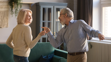 Happy middle aged couple, grey haired smiling wife and husband dancing to favorite music, having fun om date at home in living room, mature man and woman spending free time, weekend together