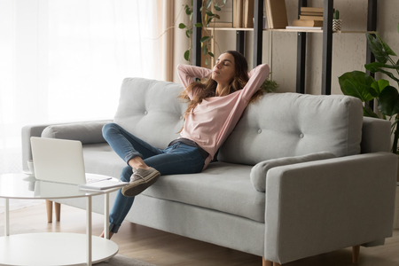 Relaxed young woman leaned on couch closed eyes putting hands behind head enjoy fresh air, freelancer resting from work in modern cozy living room alone, daydream day nap, fall asleep or pause concept Stock Photo