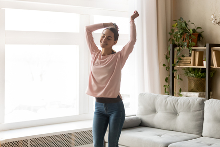 Carefree woman smiles dances with closed eyes raises hands holds phone or remote control from player listens playlist music track moving in living room enjoy life mood spend free time at home concept.