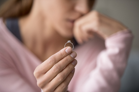 Upset woman holding wedding ring close up cropped image, took off jewellery demonstrate show it as symbol of divorce family split break up, legally dissolve wifehood with husband, bustup of a marriage