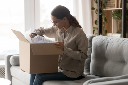 Woman in glasses sit on couch in living room holds big carton box on laps looks inside unpack goods, satisfied client buyer received ordered online via internet items, postal delivery service concept