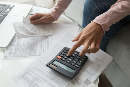 Close up cropped image coffee table full with papers invoices cheque bills, female hands holding receipt calculating company expenses results of incomes, bookkeeper accountant doing paperwork concept Stock Photo