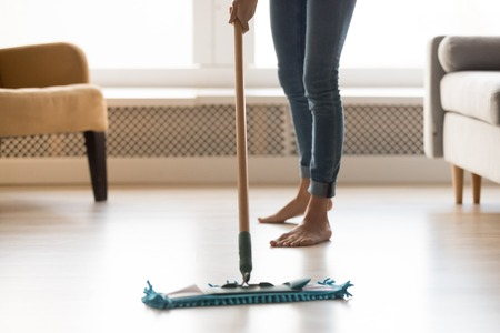 Close up cropped image of barefoot woman in casual clothes make house chores cleaning warm heated wooden laminate floor using wet mop, doing routine home work and housekeeping specialist job concept